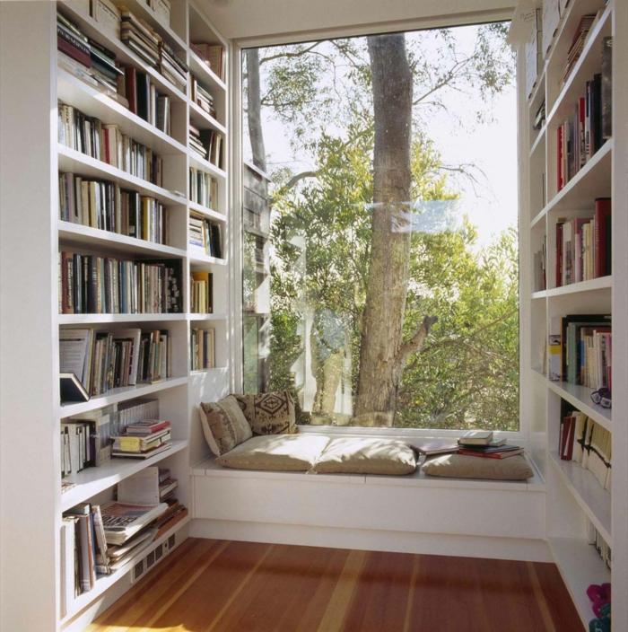 coin lecture cosy baigné de lumière sous une grande fenêtre