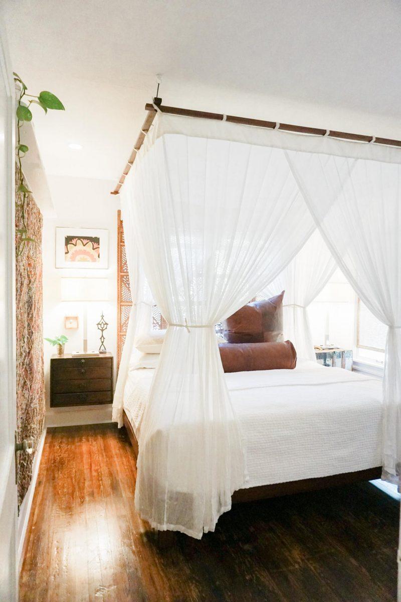 chambre de style colonial avec lit baldaquin et rideaux fins blancs