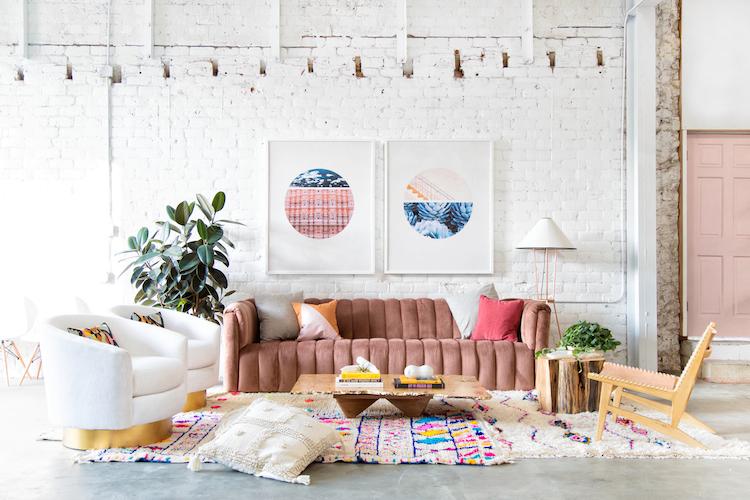 grand canapé en velours couleur rose dans une grande pièce avec mur en briques blanches