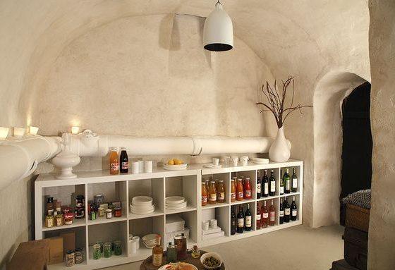 meuble de rangement blanc pour ranger bouteilles et bocaux dans un aménagement cave blanche