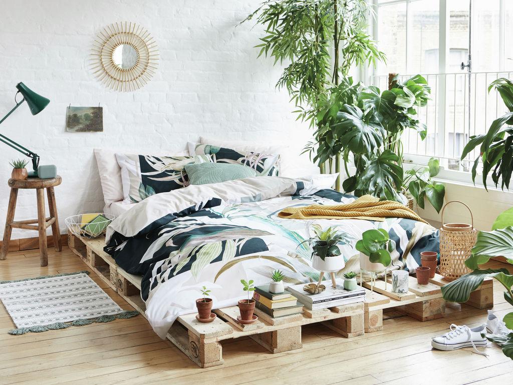 plantes décoratives dans une chambre à lit en palettes de bois