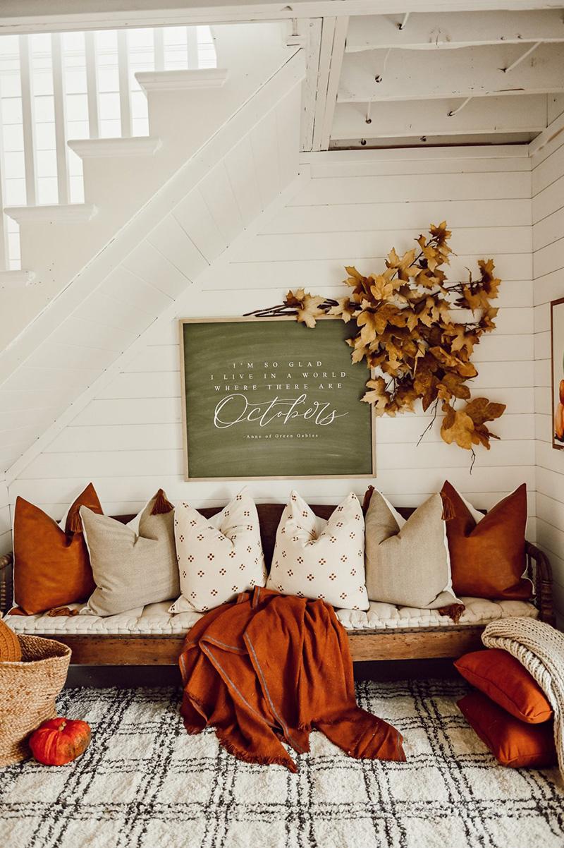 coussins et plaids couleur crème et orange sur une banquette en bois dans un salon déco automne