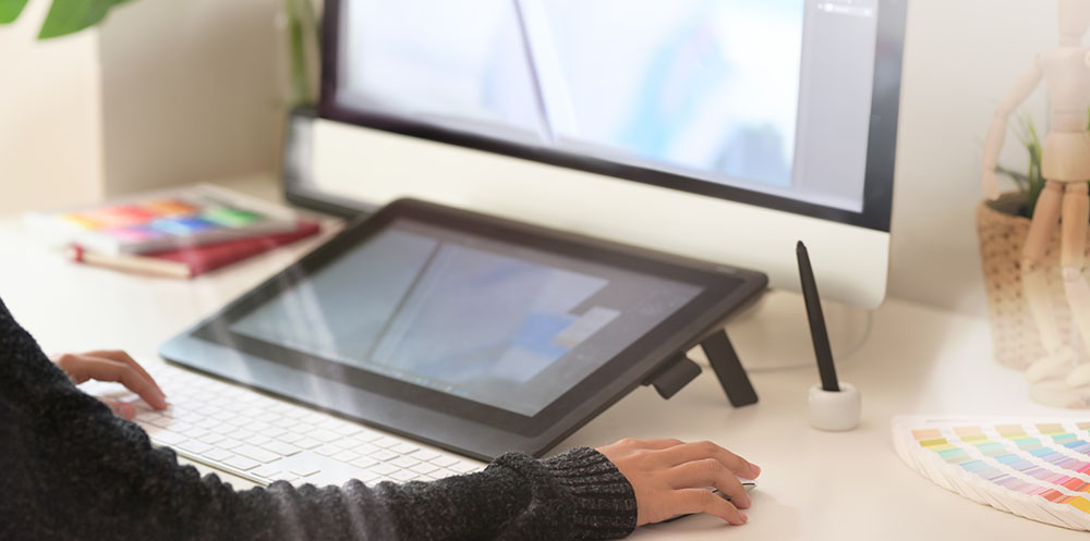 Personne travaillant sur une tablette connecte à un ordinateur